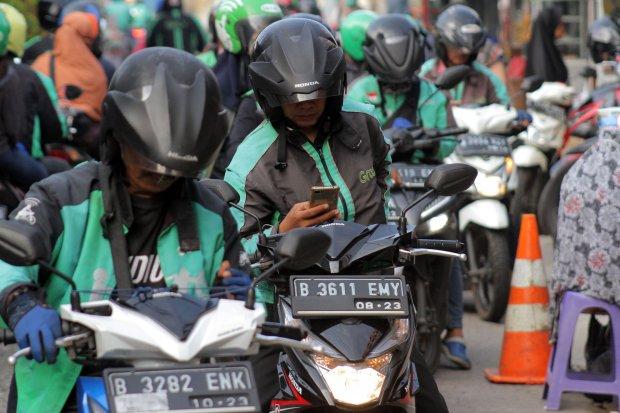 Sejumlah pengemudi ojek daring (online) menunggu penumpang di depan Stasiun Pondok Cina, Kota Depok, Jawa Barat, Selasa (11/6/2019). Kementerian Perhubungan (Kemenhub) segera mengeluarkan aturan larangan diskon pada transportasi online, termasuk ojek onli
