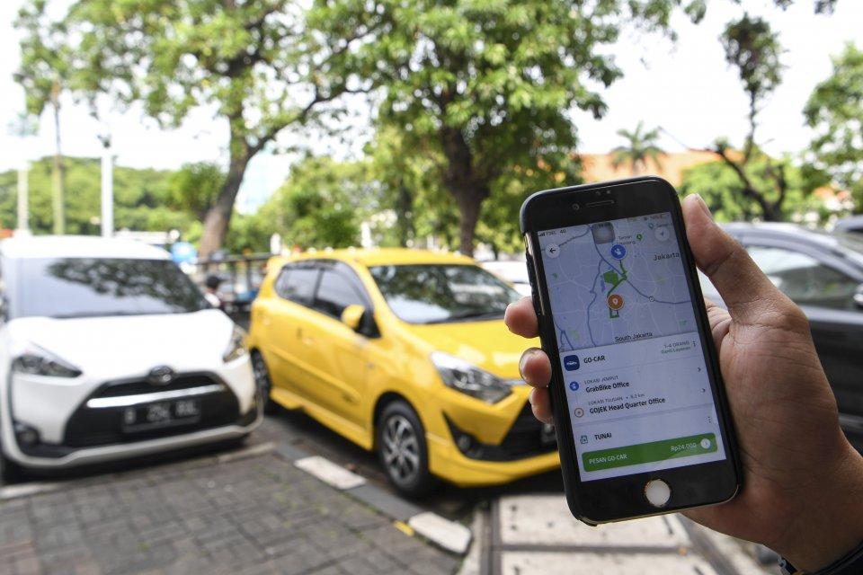 Pengemudi taksi online Gojek dan Grab mengeluh pendapatan turun akibat perluasan area ganjil genap di DKI Jakarta.