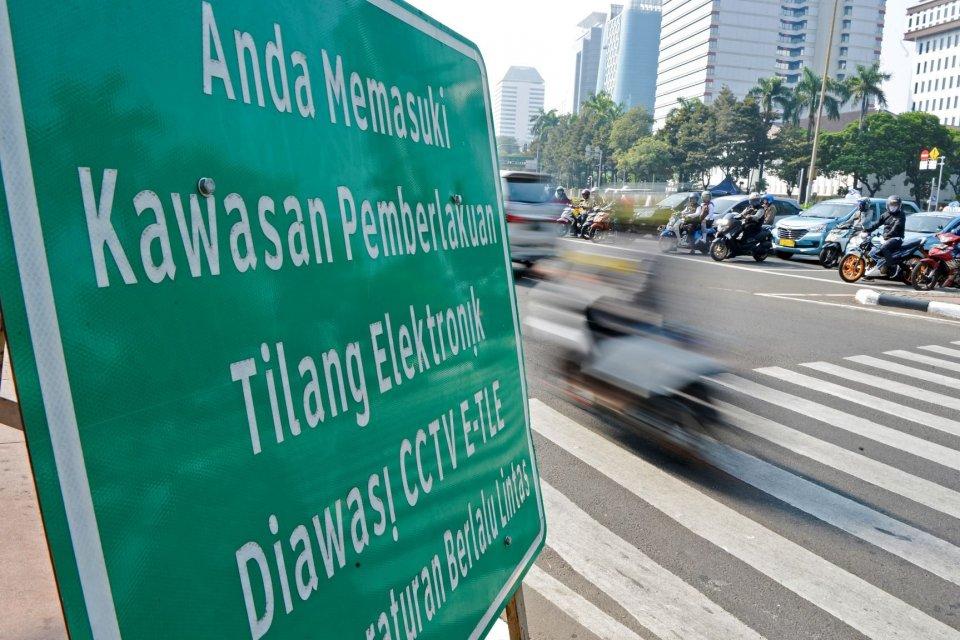 Pengendara melintas di dekat rambu tilang elektronik di kawasan Jalan Medan Merdeka Barat, Jakarta, Senin (1/7/2019). Direktorat Lalu Lintas Polda Metro Jaya menerapkan penilangan dengan sistem Electronic Traffic Law Enforcement (ETLE) dengan memasang 10