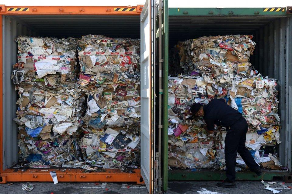 Petugas menunjukkan kertas bekas (waste paper) impor yang dikirim dari Australia di lapangan penumpukkan kontainer di PT Terminal Petikemas Surabaya (TPS) di Surabaya, Jawa Timur, Selasa (9/7/2019). Kantor Pengawasan dan Pelayanan Bea dan Cukai (KPPBC) Ti
