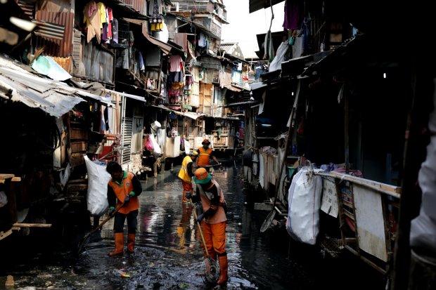 Petugas Kebersihan membersihkan sampah di kawasan permukiman padat penduduk, bantaran Kali Krukut Bawah, Kebon Melati, Tanah Abang, Jakarta Pusat (15/7). Badan Pusat Statistik (BPS) mencatat jumlah penduduk dengan pengeluaran per kapita per bulan di bawah