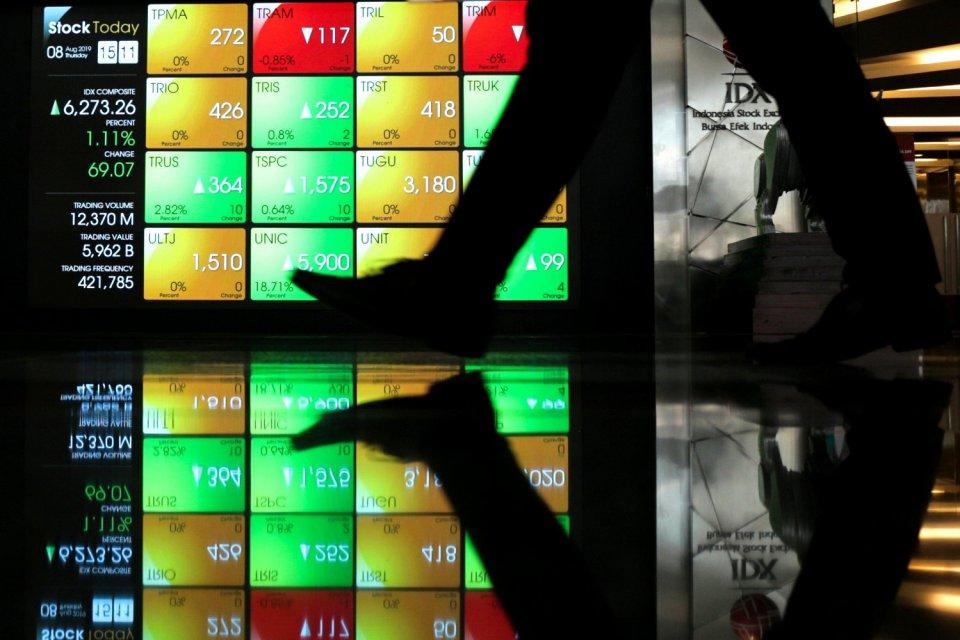 Seorang pekerja melintas di layar elektronik pergerakan saham di Bursa Efek Indonesia. IHSG selama sepekan terkoreksi 0,92%. Saham Garuda Indonesia dan Antam mencatatkan diri dalam jajaran saham paling cuan selama sepekan perdagangan.