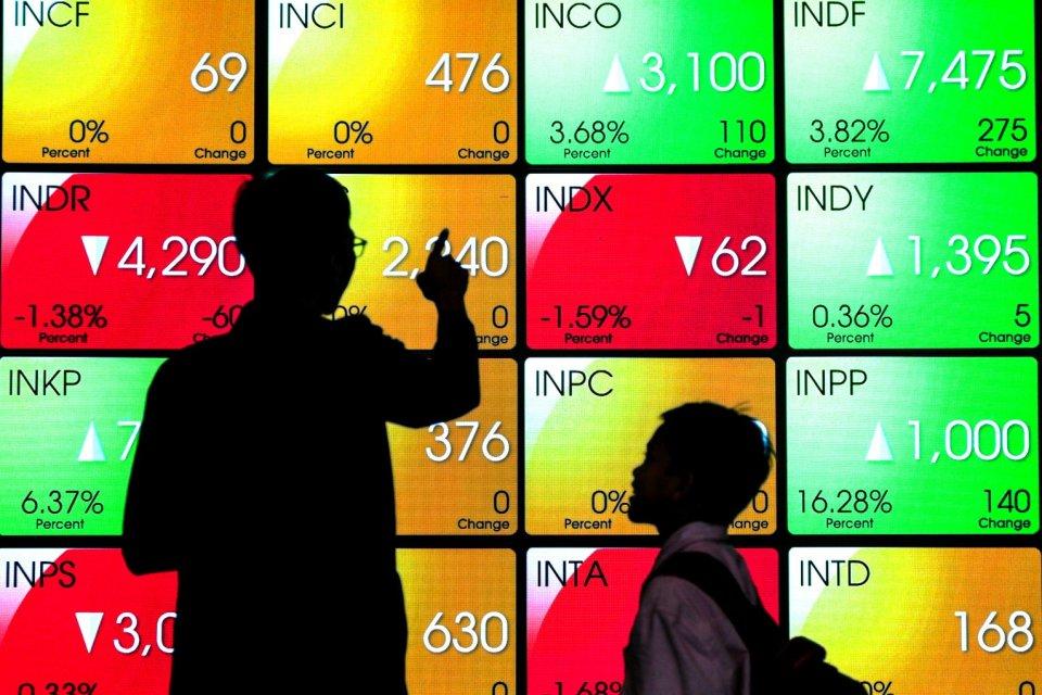 Seorang pekerja melintas di layar elektronik pergerakan saham di Bursa Efek Indonesia, Sudirman, Jakarta Pusat (08/08). IHSG tercatat menguat 1,38% ke 6.204,19. IHSG masih didera aksi jual asing mencatat jual bersih Rp 214,41 miliar.