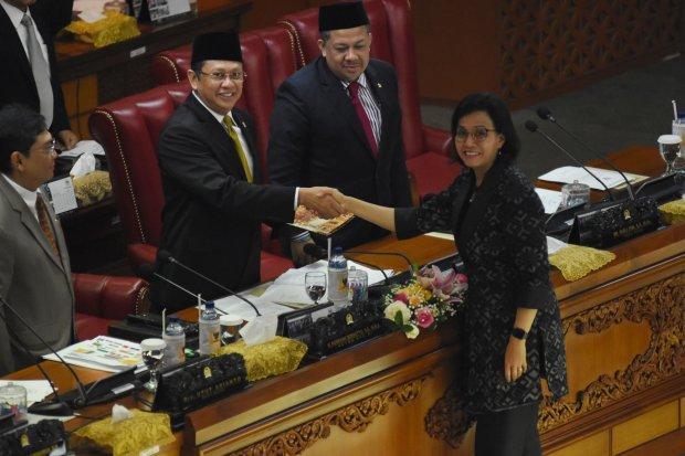 Menteri Keuangan Sri Mulyani Indrawati (kanan) menyalami Ketua DPR Bambang Soesatyo (kiri) usai menyampaikan pidato tanggapan pemerintah terhadap pandangan fraksi-fraksi terkait RUU APBN tahun 2020 disaksikan Ketua DPR Bambang Soesatyo (kedua kiri) didamp