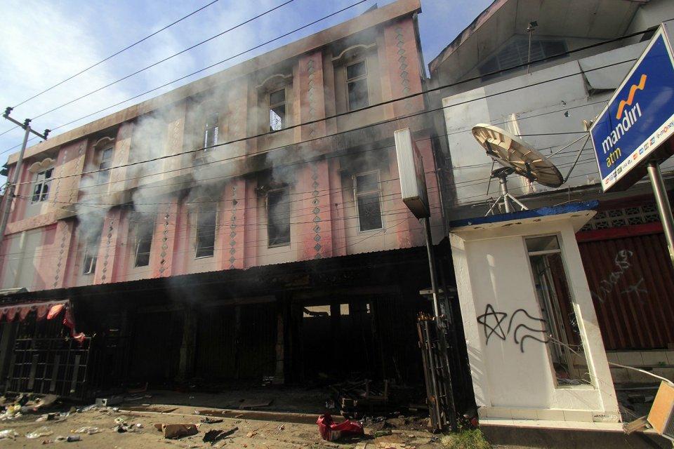 Asap masih mengepul dari sebuah bangunan yang terbakar di Jayapura, Papua, Jumat (30/8/2019). Sejumlah bangunan dan kendaraan terbakar saat aksi unjuk rasa yang berakhir rusuh, di Jayapura, Kamis (29/8/2019).