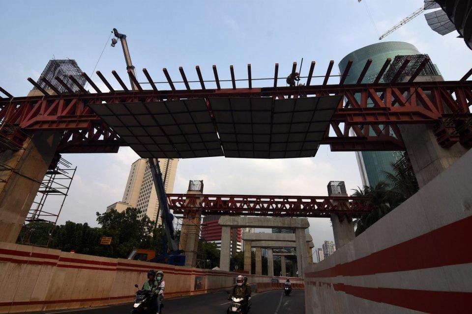 Pekerja memasang rangka untuk konstruksi tiang pancang Light Rail Transit (LRT) Jabodebek di kawasan Rasuna Said, Kuningan, Jakarta, Jumat (13/9/2019). Hingga September 2019, Adhi Karya baru meraih 25% dari target kontrak baru perusahaan yang dipatok Rp 3