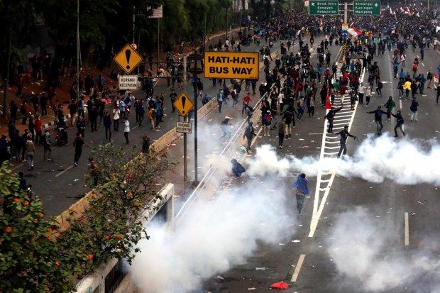 Polisi melontarkan gas air mata saat kericuhan dalam unjuk rasa di depan kompleks Parlemen di Jakarta, Selasa (24/9/2019). Ribuan mahasiswa yang berasal dari kampus di sejumlah daerah itu turun ke jalan berdemonstrasi menolak UU KPK dan pengesahan RUU KUH