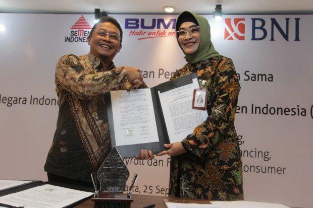 Direktur Hubungan Kelembagaan BNI Adi Sulistyowati (kanan) dan Direktur Strategi Bisnis & Pengembangan Usaha Semen Indonesia Fadjar Judisiawan (kiri) menandatangani perjanjian kerja sama (PKS) pelayanan jasa notional pooling dan pemberian fasilitas supply