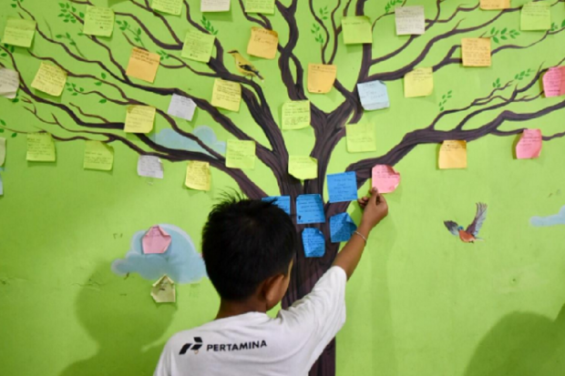 Seorang anak sedang menempel kertas di pohon. Pertamina menggelar tiga program Corporate Social Responsibility (CSR) dengan menggandeng sejumlah kelompok serta instansi setempat guna memberdayakan serta membantu pemulihan trauma para ibu dan anak-anak di