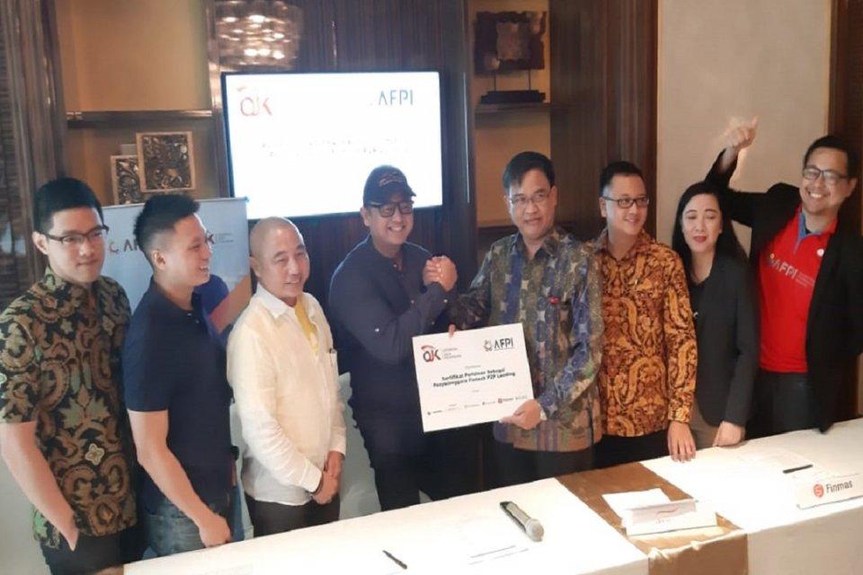 Asosiasi fintech pendanaan indonesia (AFPI) dan Direktur Pengaturan Perizinan dan Pengawasan Fintech OJK Hendrikus Passagi, bersama keenam anggotanya yang baru memperoleh izin usaha usai konferensi pers di kantornya, Jakarta, Kamis (10/10). Ada 13 fintech