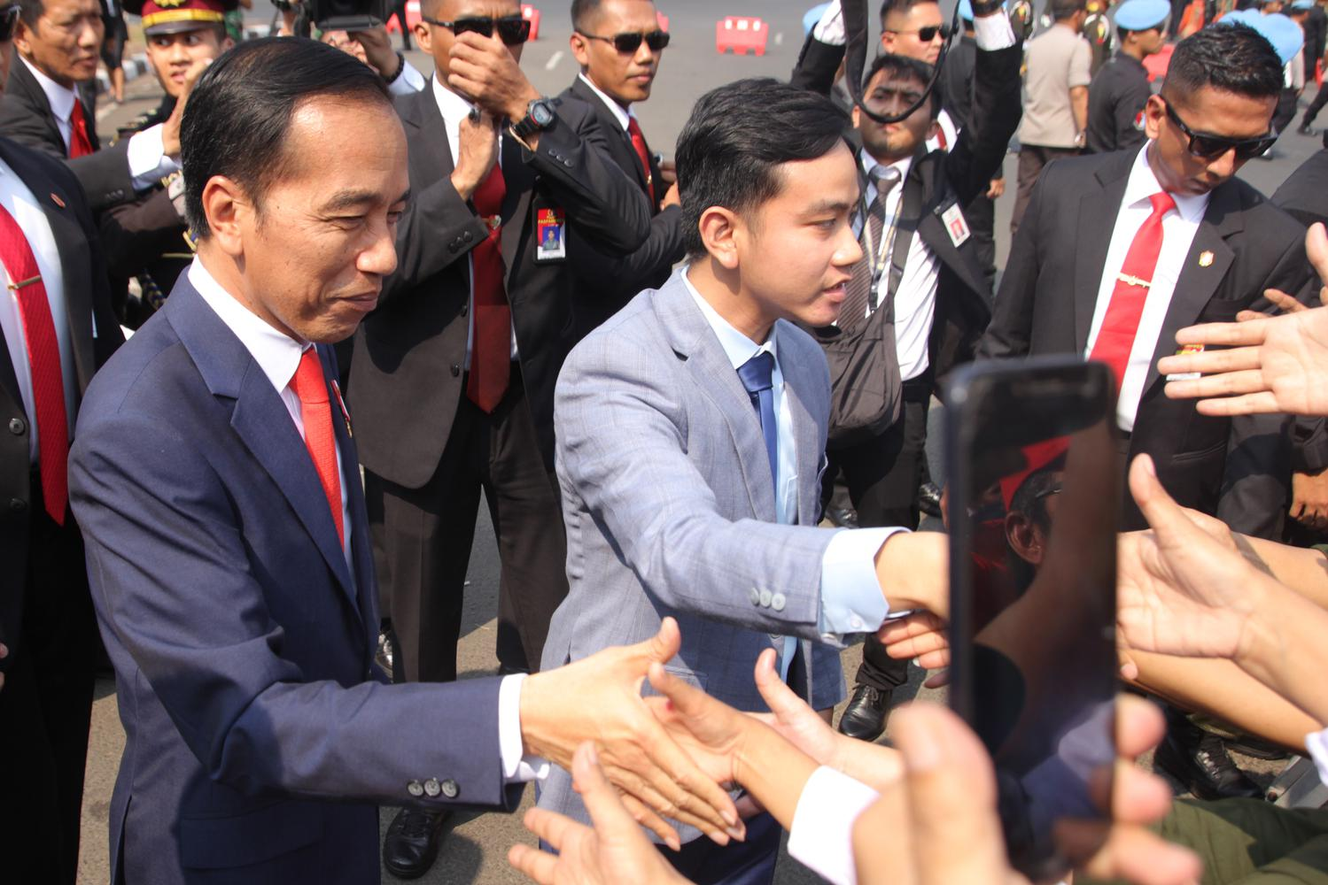 Presiden Joko Widodo (kiri) didampingi putranya Gibran Rakabuming (kanan) menyalami warga sebelum mengikuti upacara pelantikan. Gibran siap menyerahkan bisnisnya ke sang adik lantaran bakal berfokus di bidang politik.