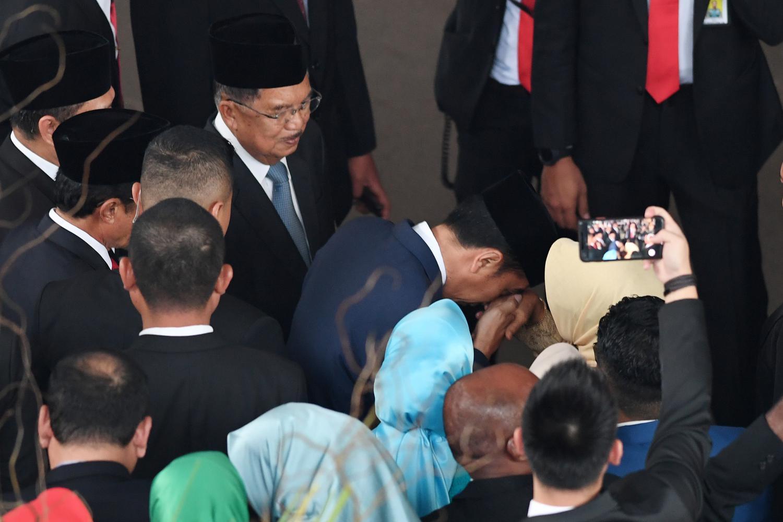 Presiden Joko Widodo (kedua kanan) mencium tangan ibunda Sudjiatmi (kanan) disaksikan mantan Wakil Presiden Jusuf Kalla usai pelantikan presiden dan wapres periode 2019-2024 kompleks Parlemen Senayan, Jakarta, Minggu (20/10/2019). Pada Rabu (25/3), Ibunda