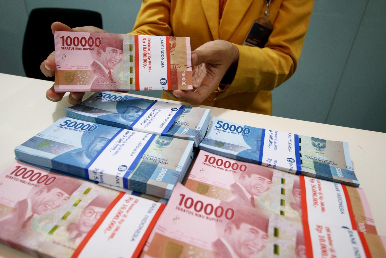 Karyawan menunjukan uang rupiah pecahan 100 ribu dan 50 ribu di Plaza Mandiri, Jakarta, Senin (23/9/2019). Nilai tukar rupiah yang ditransaksikan antar bank di Jakarta pada awal pekan ini dibayangi sentimen perang dagang, terkait batalnya kunjungan deleg