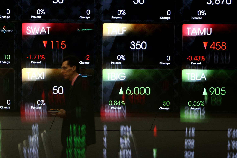 Karyawan berjalan di dekat layar pergerakan saham di gedung Bursa Efek Indonesia, Jakarta, Kamis (26/9/2019). Indeks Harga Saham Gabungan (IHSG) pada perdagangan hari ini, Kamis (26/9/2019) ditutup menguat 1,37 persen ke level 6.230,33.