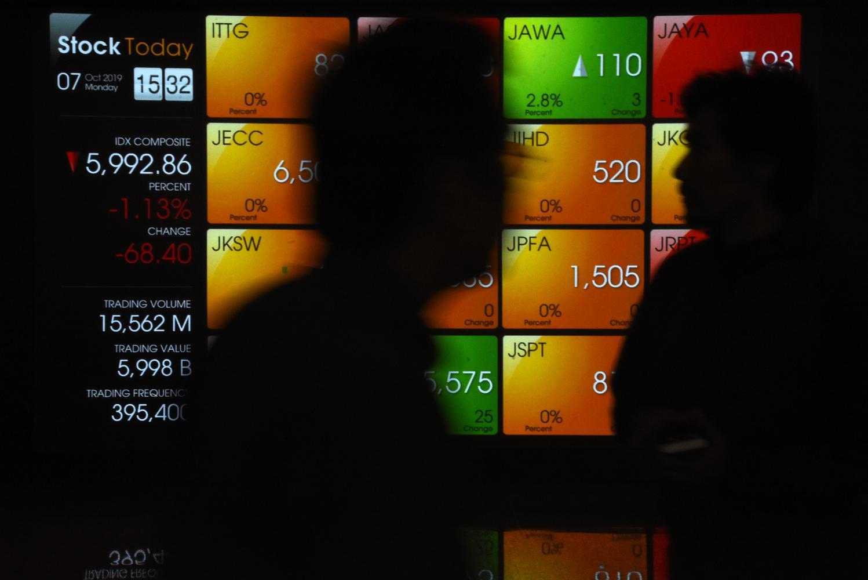 Pegawai melintas di depan layar pergerakan saham di gedung Bursa Efek Indonesia, Jakarta, Senin (7/10/2019). Indeks Harga Saham Gabungan (IHSG) ditutup melemah satu persen atau turun 60,67 poin ke level 6.000,58 dari perdagangan akhir pekan lalu, Jumat (4