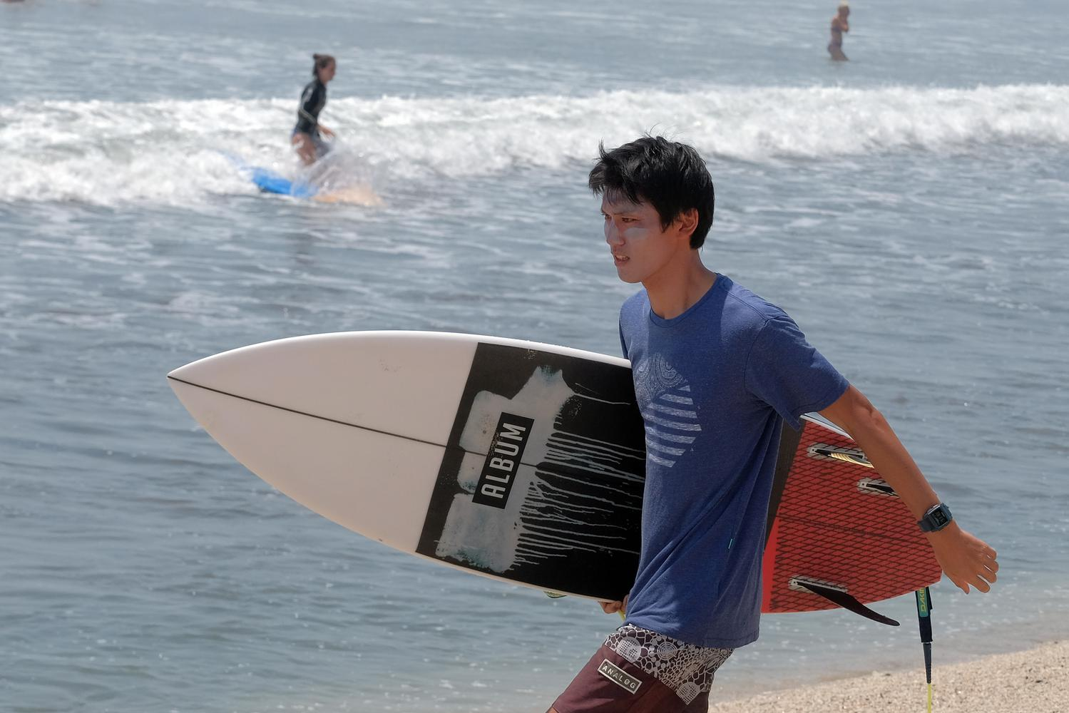 Wisatawan menggunakan krim pelindung kulit untuk mengurangi dampak sengatan sinar matahari saat berselancar di Pantai Kuta, Badung, Bali, Kamis (24/10/2019). Badan Meteorologi, Klimatologi, dan Geofisika (BMKG) menyatakan cuaca panas yang melanda wilayah