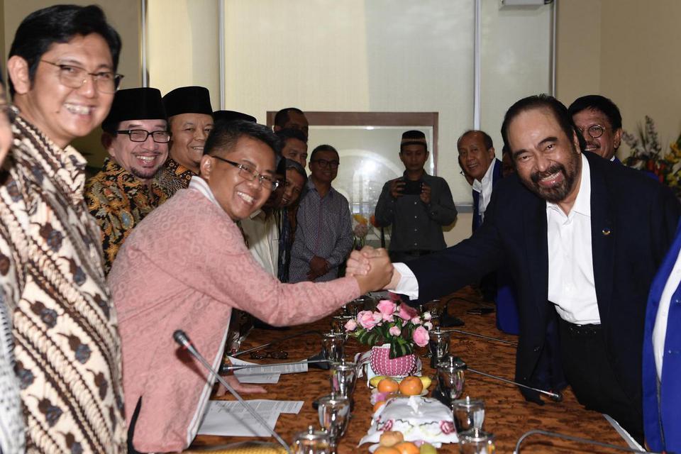 Ketum Partai Nasdem Surya Paloh (kanan) berjabat tangan dengan Presiden PKS Sohibul Iman (kedua kiri). Kendati telah bertemu PKS, Nasdem menyatakan partainya tetap berada di dalam koalisi pemerintah.