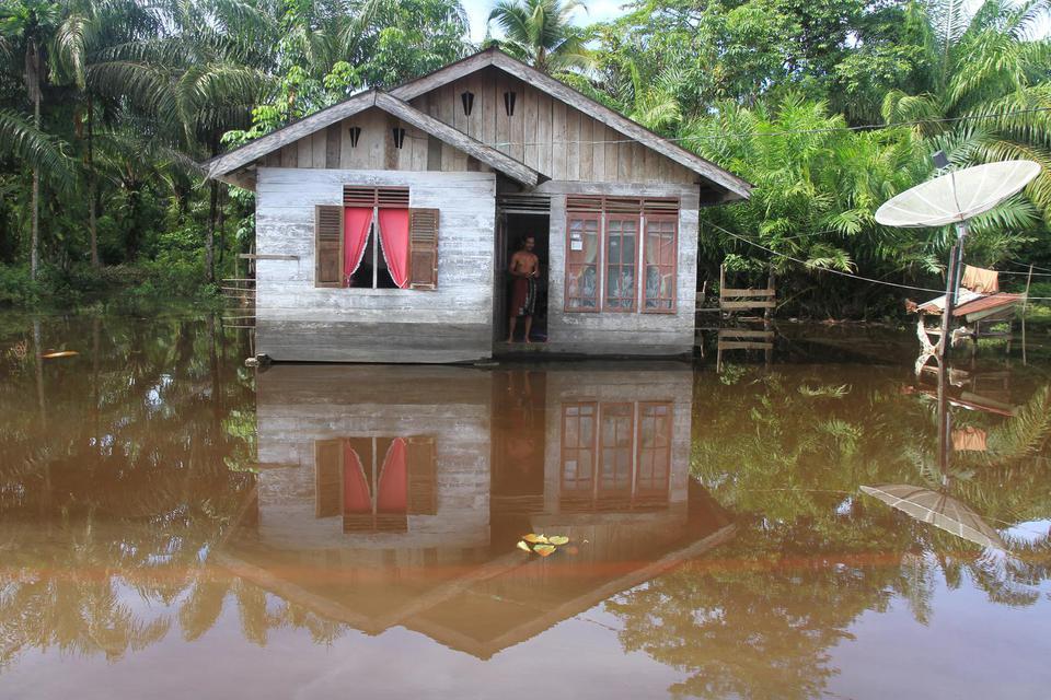 Warga berada di rumahnya yang terendam banjir di Desa Gunong Pulo, Kecamatan Arongan Lam Balek, Aceh Barat, Aceh, Kamis (31/10/2019). Banjir yang disebabkan tingginya intensitas hujan sejak dua pekan terakhir menyebabkan ratusan rumah warga dan ratusan he