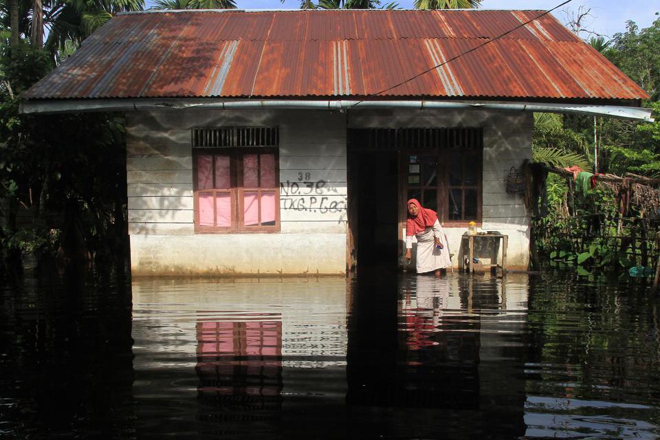 Warga berada di depan rumahnya yang terendam banjir di Desa Gunong Pulo, Kecamatan Arongan Lam Balek, Aceh Barat, Aceh, Kamis (31/10/2019). Banjir yang disebabkan tingginya intensitas hujan sejak dua pekan terakhir menyebabkan ratusan rumah warga dan ratu