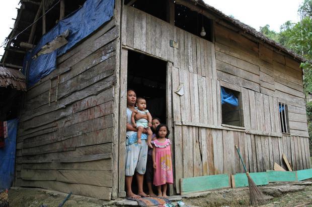 Darmayanti bersama tiga orang anak yang belum pernah mendapatkan bantuan apapun dari Dana Desa berada di pintu rumahnya di Desa Andobeu Jaya, Kecamatan Anggomoare, Kabupaten Konawe, Sulawesi Tenggara, Kamis (7/11/2019).