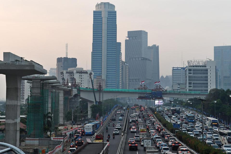 Sejumlah kendaraan bermotor melintas dengan latar belakang pembangunan \'longspan\' atau bentangan beton panjang lintasan Light Rail Transit (LRT) di Kuningan, Jakarta, Kamis (7/11/2019). Menurut situs resmi LRT Jabodebek, lintasan LRT Kuningan merupakan