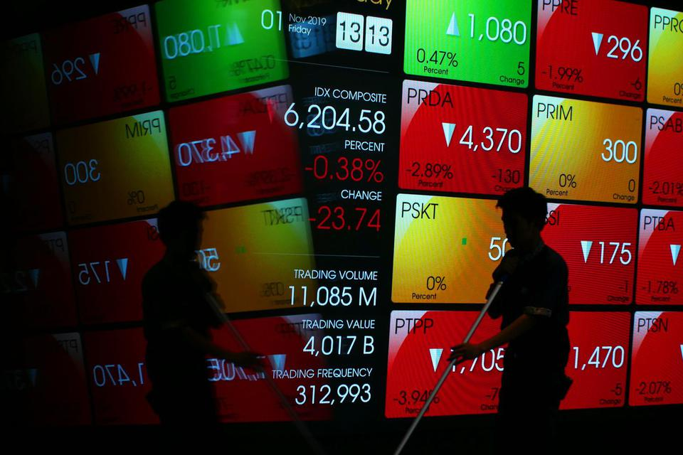 Pekerja berjalan di dekat layar pergerakan saham di gedung Bursa Efek Indonesia, Jakarta, Jumat (1/11/2019). Indeks Harga Saham Gabungan (IHSG) pada perdagangan hari Jumat (1/11/2019) ditutup melemah 21 poin (0,34 persen) ke level 6.207.