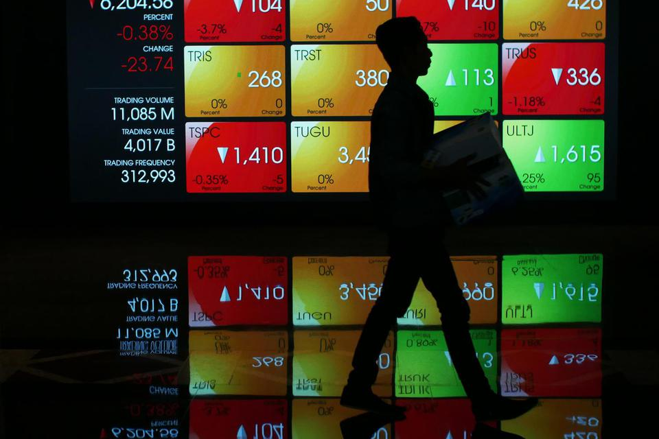 Karyawan berjalan di dekat layar pergerakan saham di gedung Bursa Efek Indonesia, Jakarta, Jumat (1/11/2019). Indeks Harga Saham Gabungan (IHSG) pada perdagangan hari Jumat (1/11/2019) ditutup melemah 21 poin (0,34 persen) ke level 6.207.