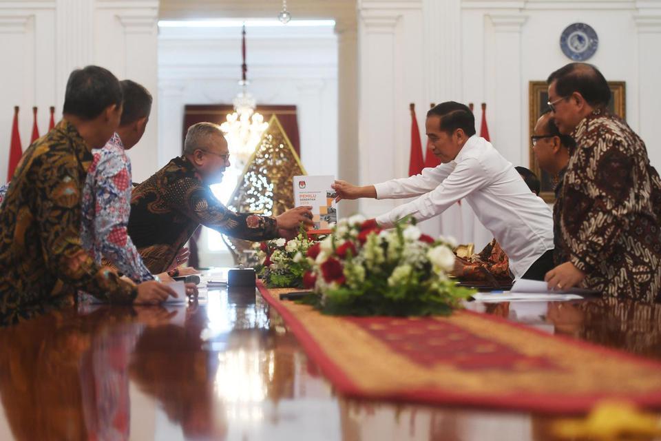 Presiden Joko Widodo (kanan) menerima buku laporan penyelenggaraan Pemilu Serentak tahun 2019 dari Ketua Komisi Pemilihan Umum (KPU) Arief Budiman dalam pertemuan di Istana Merdeka, Jakarta, Senin (11/11/2019). Dalam pertemuan itu pimpinan KPU memberikan