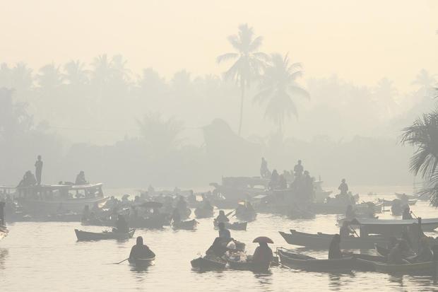 Suasana pasar terapung yang diselimuti kabut asap di desa Lok Baintan, Kabupaten Banjar, Kalimantan Selatan, Sabtu (9/11/2019). Kebakaran hutan dan lahan (Karhutla) yang terjadi di sejumlah daerah Provinsi Kalsel mengakibatkan kabut asap yang menggangu ak