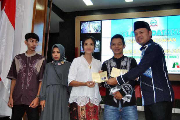 Wali Kota Bogor Bima Arya (kanan) menyerahkan buku nikah kepada peserta itsbat dan nikah massal di Bogor, Jawa Barat, Sabtu (16/11/2019). Aktivis Aliansi Masyarakat Adat Nusantara (AMAN), menilai pemerintah mengintervensi terlalu jauh dalam wacana penerap