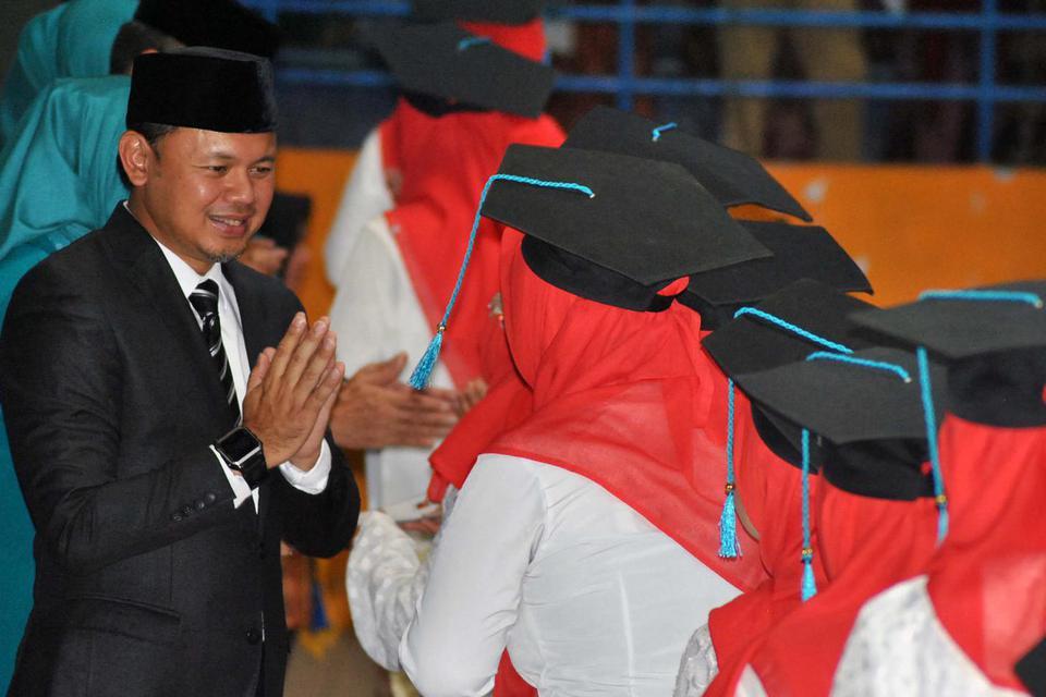 Wali Kota Bogor Bima Arya (kiri) bersalaman dengan sejumlah peserta saat prosesi wisuda Sekolah Ibu di GOR Indoor Basket Pajajaran, Kota Bogor, Jawa Barat, Selasa (26/11/2019).