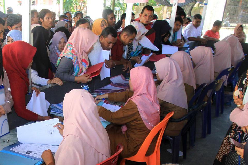 Puluhan pelamar Calon Pegawai Negeri Sipil (CPNS) antre untuk menyerahkan berkas pendaftaran lamaran di halaman komplek Dinas Pendidikan Kabupaten Aceh Barat, di Aceh, Senin (25/11/2019). Menurut keterangan panitia seleksi penerimaan CPNS Kabupaten Aceh B