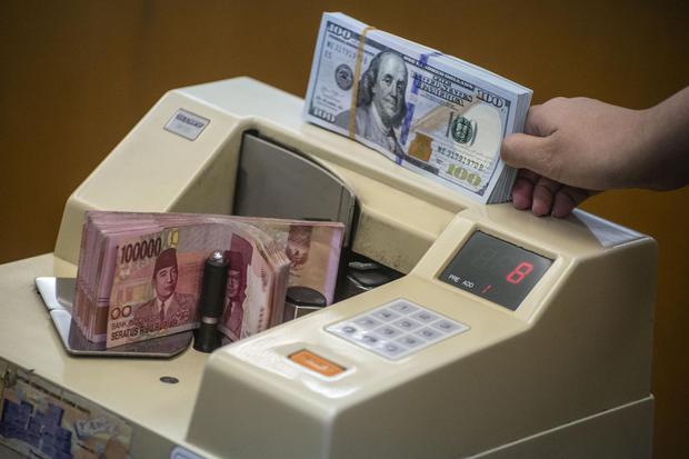 Petugas mengitung uang rupiah di salah satu gerai penukaran uang asing di Jakarta, Rabu (27/11/2019). Kementerian Keuangan mencatat realisasi penerimaan pajak dari Januari hingga Oktober 2019 hanya tumbuh 0,23 persen menjadi Rp1.018,47 triliun atau 64,56