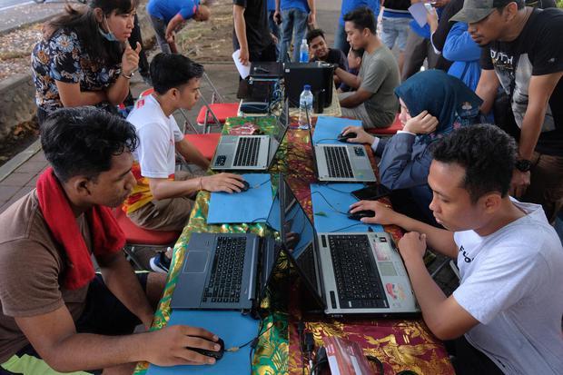 Warga mencoba menjawab soal saat mengikuti simulasi Computer Assisted Test (CAT) dalam sosialisasi seleksi CPNS 2019 pada hari bebas kendaraan, di Denpasar, Bali, Minggu (3/11/2019). Pemerintah akan membuka portal pendaftaran CPNS malam nanti pukul 23.11