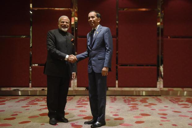 Presiden Joko Widodo (kanan) berjabat tangan dengan Perdana Menteri India Narendra Modi, sebelum pertemuan bilateral disela KTT ke-35 ASEAN di Bangkok, Thailand, Minggu (3/11/2019). Perdana Menteri India, Narendra Modi mengumumkan kebijakan lockdown selam