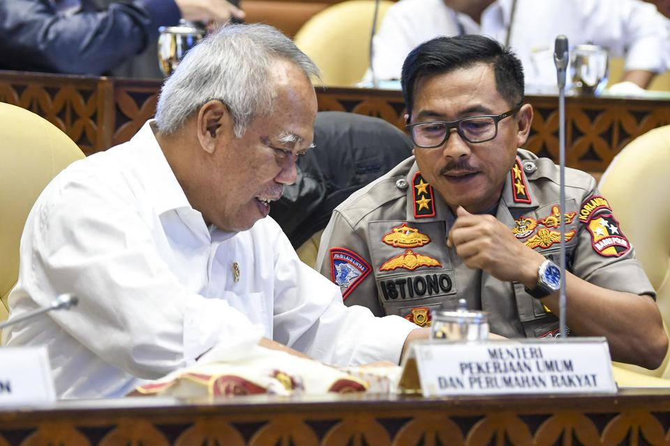 Menteri PUPR Basuki Hadimuljono (kiri) berbincang dengan Kakorlantas Polri Irjen Pol Istiono (kanan) saat mengikuti Rapat Kerja dengan Komisi V DPR di Kompleks Parlemen, Jakarta, Senin (2/12/2019). Raker tersebut membahas kesiapan infrastruktur dan transp
