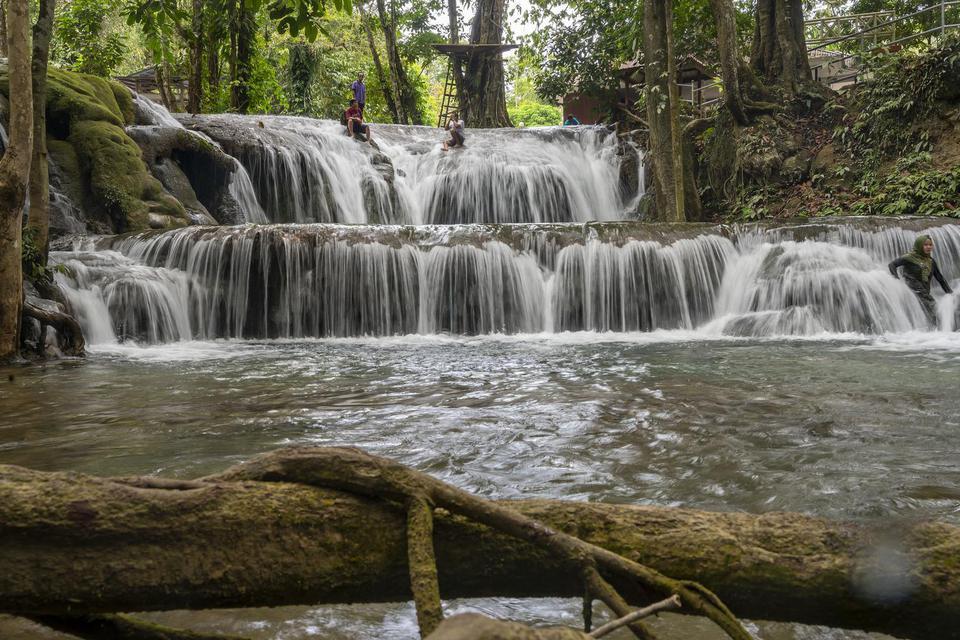 Sejumlah wisatawan mandi di obyek wisata pemandian alam Salodik, Luwuk Utara, Kabupaten Banggai, Sulawesi Tengah, Kamis (5/12/2019).