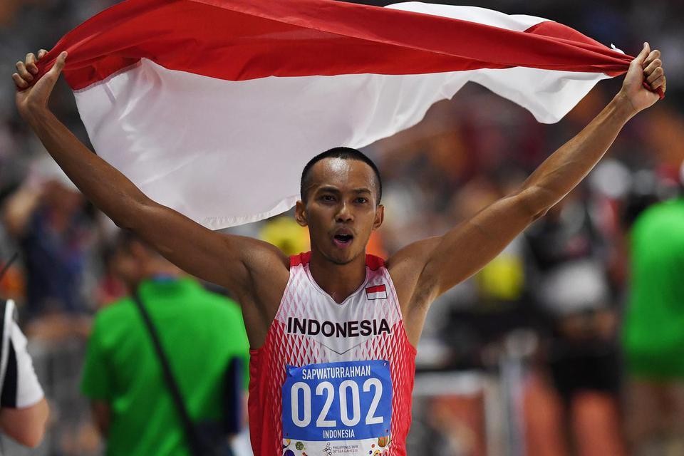 Atlet lompat jauh Indonesia Sapwaturrahman mengibarkan Bendera Merah Putih setelah berhasil memenangkan pertandingan Lompat Jauh Putra SEA Games ke-30 di Stadion Atletik New Clark, Filipina, Sabtu (7/12/2019).