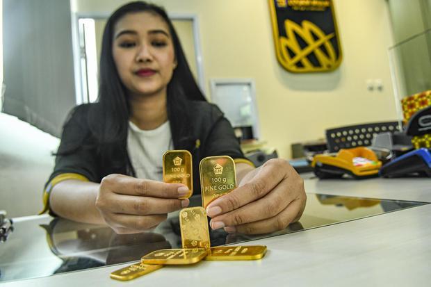 Petugas menunjukkan sampel emas batangan di Butik Emas Logam Mulia, Jakarta, Senin (9/12/2019). Harga emas batangan PT Aneka Tambang (Persero) Tbk pada Senin (9/12) Rp 744.000 per gram, turun Rp 3.000 dibandingkan harga emas pada Minggu (8/12).