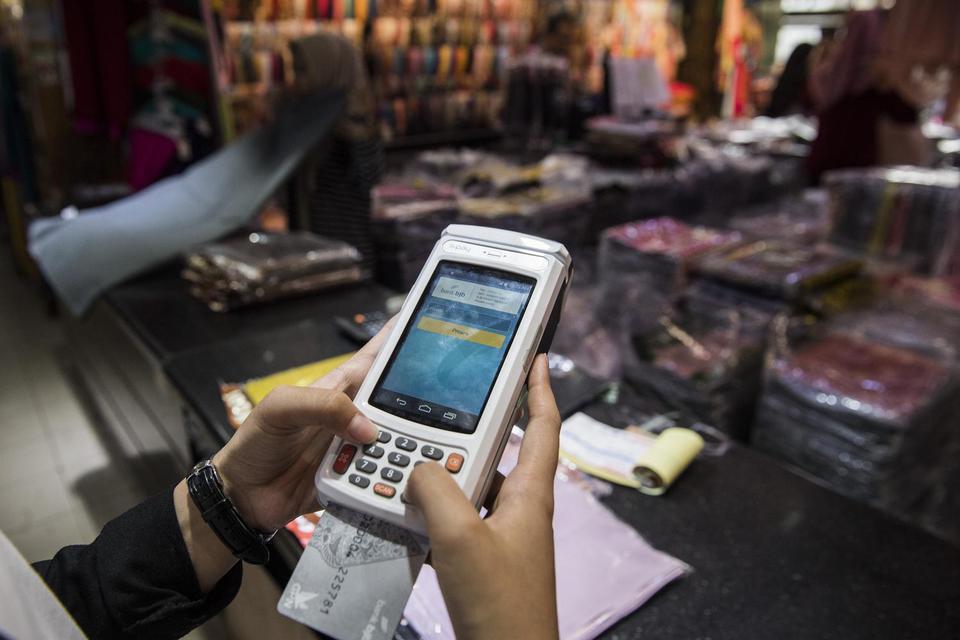 Pembeli melakukan transaksi pembayaran digital dengan mesin EDC berbasis android di Pasar Baru, Bandung, Jawa Barat, Senin (16/12). Bank BJB meluncurkan pembayaran digital dengan menggunakan Quick Response Code Indonesian Standard (QRIS), bjb EDC berbasis