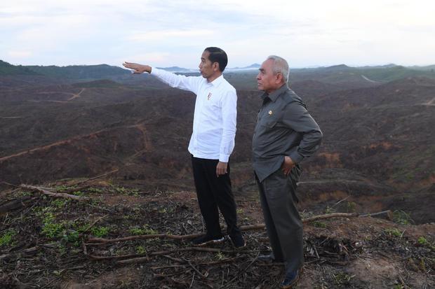 Presiden Joko Widodo (kiri) berbincang dengan Gubernur Kalimantan Timur Isran Noor (kanan) saat meninjau lokasi rencana ibu kota baru di Sepaku, Penajam Paser Utara, Kalimantan Timur, Selasa (17/12/2019).