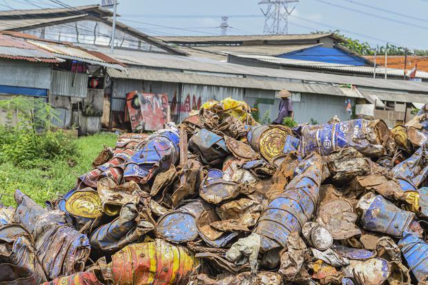 Warga beraktivitas di antara tumpukan limbah Bahan Beracun dan Berbahaya (B3) di Jakarta, Jumat (27/12/2019). Limbah B3 dari kegiatan industri maupun rumah tangga yang terbuang ke lingkungan akan berdampak pada pencemaran dan kesehatan manusia.