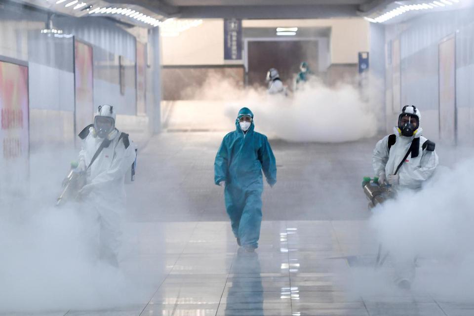 Sukarelawan memakai baju pelindung menyemprot disinfektan di stasiun kereta saat negeri tersebut sedang terjadi penularan virus korona baru, di Changsha, provinsi Hunan, China, Selasa (4/2/2020).