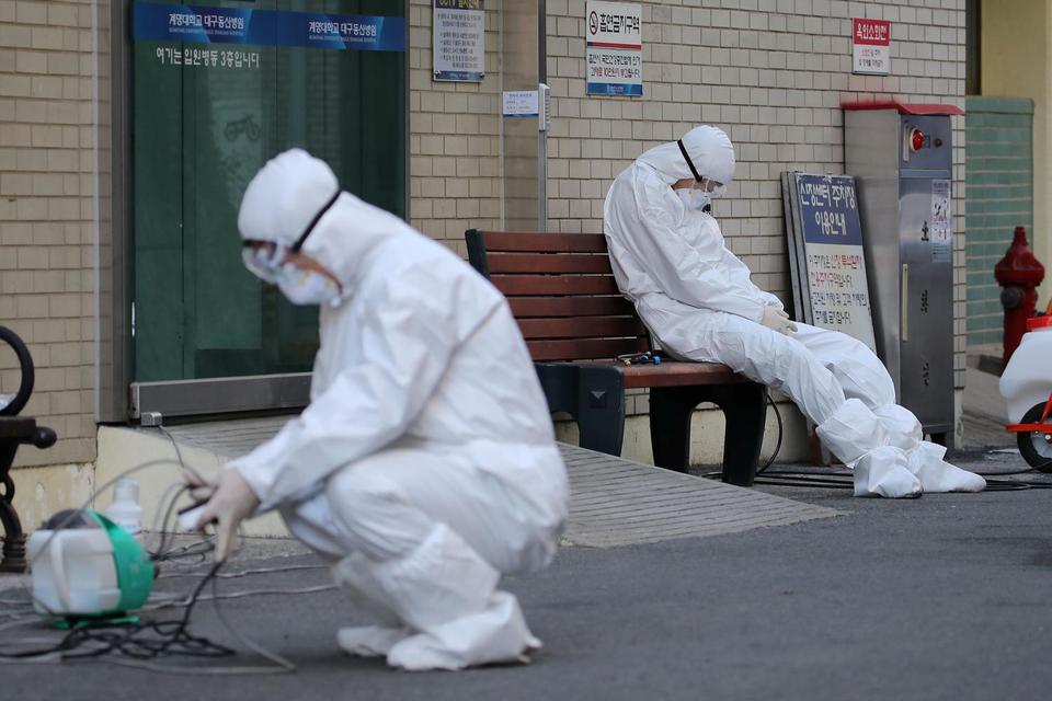 Seorang staf medis beristirahat di luar sebuah rumah sakit di Daegu, Korea Selatan. Hingga Jumat (3/4), jumlah kasus positif virus corona di dunia telah menembus angka 1 juta, dengan total meninggal dunia mencapai 52.982 orang.