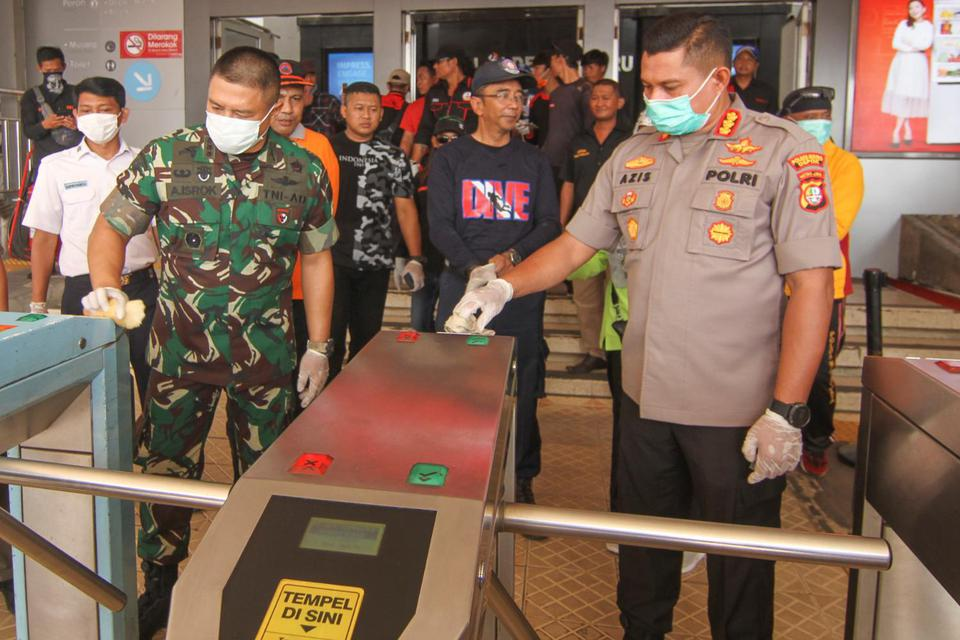 Kapolrestro Depok Kombes Pol Azis Andriansyah (kanan) bersama Dandim 0508/Depok Kolonel Inf Agus Isrok (kiri) membersihkan tempat masuk di Stasiun Depok Baru, Depok, Jawa Barat, Minggu (15/3/2020). Kegiatan yang melibatkan sejumlah anggota TNI, Polri, dan