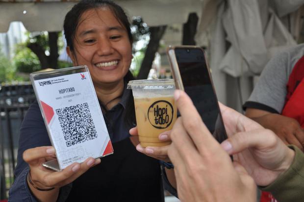 Seorang pedagang minuman kopi melayani warga yang menggunakan pembayaran non tunai Quick Response Indonesia Standard (QRIS) pada Pekan QRIS Nasional 2020 di Medan, Sumatera Utara, Minggu (15/3/2020). Bank Indonesia memperkenalkan penggunaan transaksi pemb