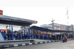 Warga mengantri panjang di salah satu halte Transjakarta di kawasan Ciledug, Tangerang.