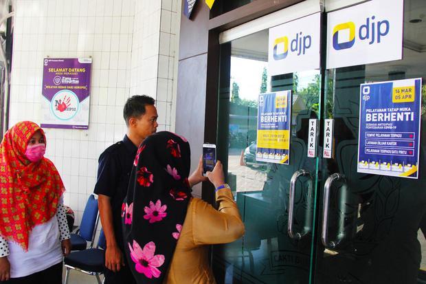 Seorang pengunjung mengambil gambar tanda pemberitahuan penghentian pelayanan pajak langsung sebagai antisipasi penyebaran COVID-19 di depan pintu masuk Kantor Pelayanan Pajak (KPP) Pratama Dumai di Dumai, Riau, Senin (16/3/2020).