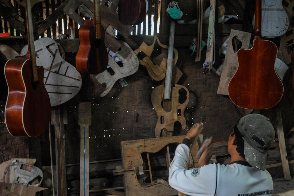 Pekerja memproduksi gitar di Workshop Guitars Gore di Lebak, Banten, Selasa (17/2/2020). OJK memberikan kelonggaran pembayaran pokok pinjaman serta bunga bagi pengusaha sektor usaha mikro kecil dan menengah (UMKM) kepada perbankan guna menyikapi dampak ne