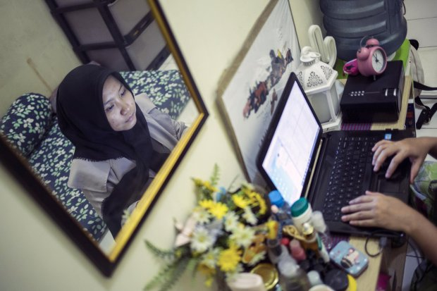 Rima Pujilestari (23), bekerja sebagai IT suport di salah satu media online di Jakarta menyelesaikan pekerjaannya di kamar indekos daerah Pejaten, Pasar Minggu, Jakarta Selatan, Kamis (19/3/2020). Sejumlah perusahaan memberlakukan Work From Home guna menc